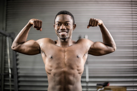 showing muscles: Athletic man showing muscles at crossfit gym Stock Photo