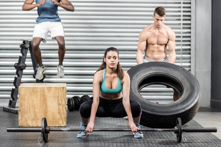 people exercising: Fit people exercising together at crossfit gym