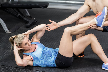sit ups: Male trainer assisting woman sit ups at crossfit gym Stock Photo