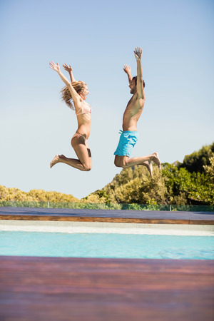 bikini couple: Happy couple jumping in the pool in a sunny day Stock Photo