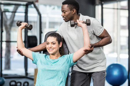 lifting weights: Athletic woman lifting weights helped by trainer at crossfit gym