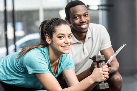 levantando pesas: Athletic woman lifting weights helped by trainer at crossfit gym