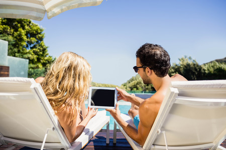 Rear view of couple using tablet on deck chairs poolside