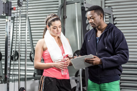 adult  body writing: Trainer and woman looking at workout plan at crossfit gym