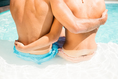 mid section: Rear view of mid section of couple embracing while sitting on pool edge
