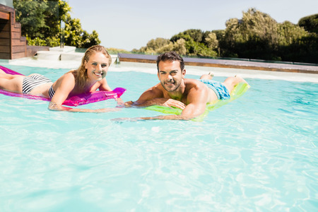 bikini couple: Happy couple with lilos in the pool in a sunny day Stock Photo