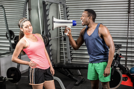 yelling: Trainer yelling at woman via megaphone at crossfit gym