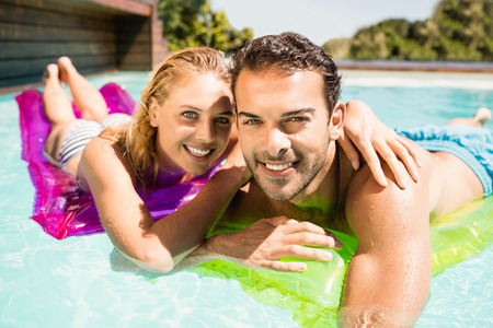 lilo: Happy couple with lilos in the pool in a sunny day Stock Photo