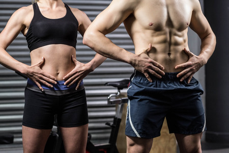 Midsection of fit couple posing at crossfit gym Reklamní fotografie