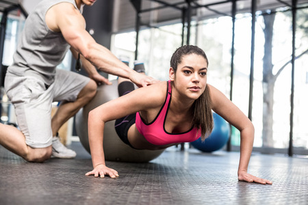 push ups: Male trainer assisting woman with push ups at crossfit gym Stock Photo