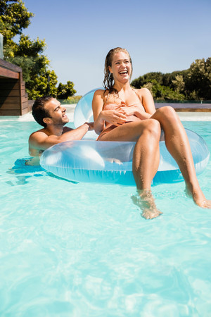 bikini couple: Happy couple in the pool with lilo in a sunny day Stock Photo