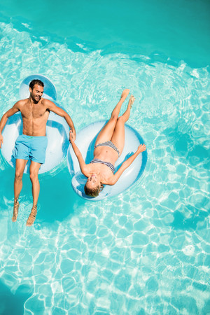 Happy couple on lilos in the pool Reklamní fotografie - 52156734