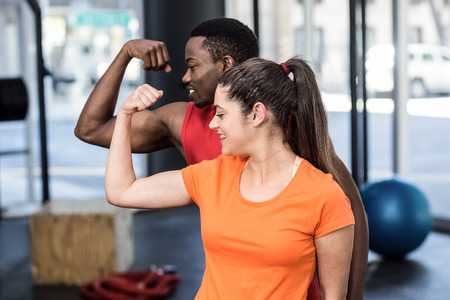 contracting: Smiling woman and man contracting biceps at crossfit gym