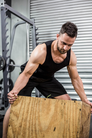 moving box: Fit man moving wooden box at crossfit gym