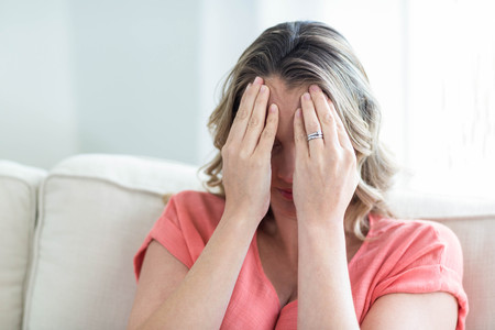 pounding head: Pregnant woman with headache on the couch Stock Photo