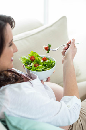 woman couch: Pregnant woman eating salad on couch Stock Photo