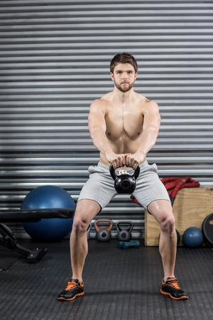 free weight: Shirtless man lifting dumbbells at crossfit gym