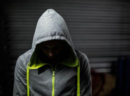 head down: Athlete wearing hood with head down at crossfit gym Stock Photo