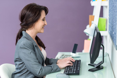 swivel chairs: Portrait of smiling pregnant woman at her computer Stock Photo