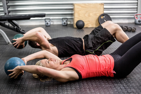 Fit Paar tun Bauch Ball Übung bei CrossFit Fitness-Studio Standard-Bild