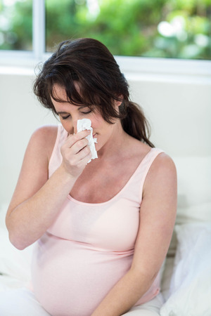 rubbing noses: Pregnant woman sitting on bed sneezing
