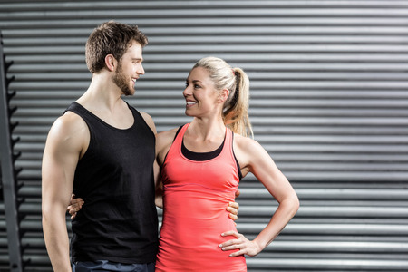 Happy fit couple embracing at crossfit gym