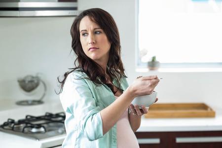 comiendo cereal: Mujer embarazada que come el cereal en la cocina