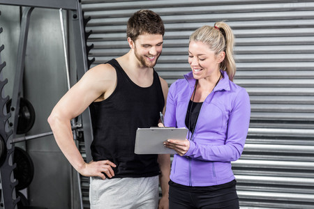 break from work: Female trainer talking with client at crossfit gym