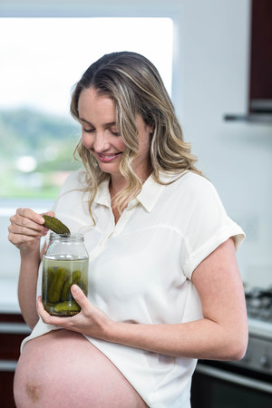 gherkins: Pregnant woman eating gherkins in the kitchen