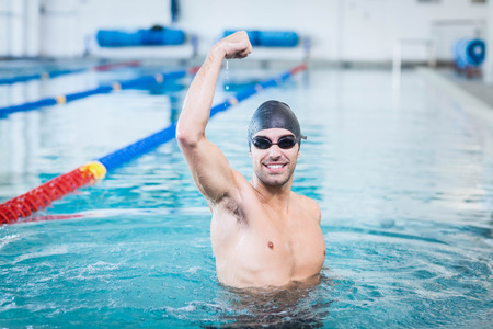 triumphing: Handsome man triumphing with raised arms in the pool