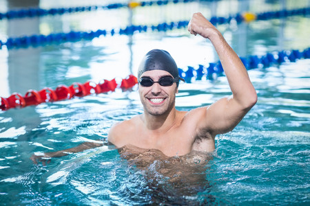 triumphing: Handsome man triumphing with raised arm in the pool Stock Photo