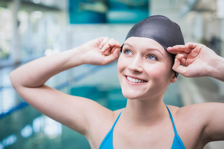 swim cap: Pretty woman putting on swim cap at the pool