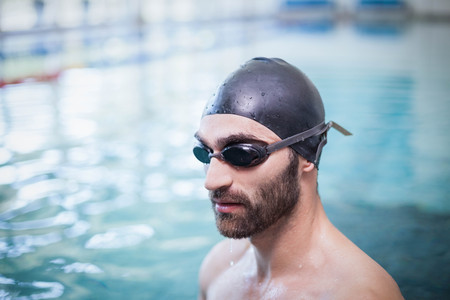swim cap: Focused man wearing swim cap and goggles at the pool Stock Photo