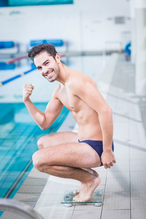 triumphing: Fit man triumphing on the weighting scale at the pool Stock Photo