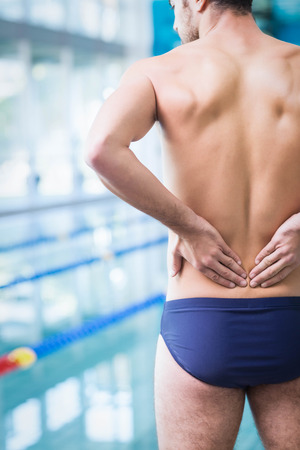 back ache: Fit man with back ache at the pool