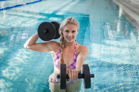 gimnasia aerobica: atractiva mujer de levantamiento de pesas en la piscina