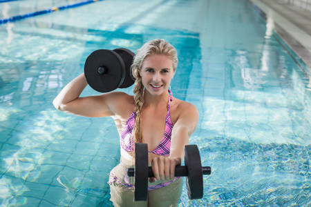 dumbbell: Attractive woman lifting dumbbells in the pool Stock Photo