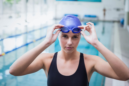 swim cap: Pretty woman wearing swim cap and goggles at the pool Stock Photo