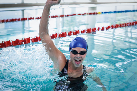 triumphing: Fit woman triumphing with raised arm at the pool Stock Photo