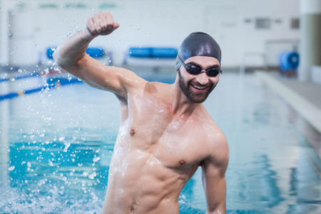 triumphing: Smiling man triumphing with raised arm at the pool Stock Photo
