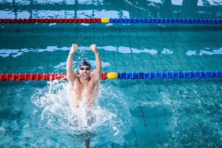 triumphing: Fit man triumphing in the pool Stock Photo