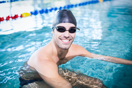 lane marker: Handsome man in the pool smiling at the camera Stock Photo
