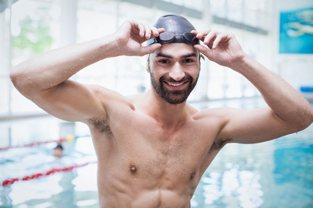 swim cap: Fit man wearing swim cap and goggles at the pool
