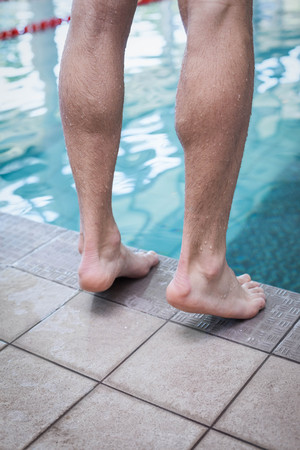 lane marker: Close up of masculine feet at the edge of a pool