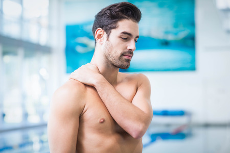 fit man: Handsome man touching his shoulder at the pool Stock Photo