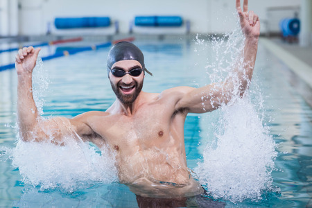 triumphing: Smiling man triumphing with raised arms at the pool