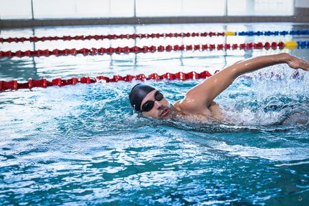 Knappe man zwemmen in het zwembad Stockfoto