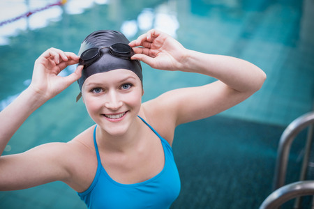 swim cap: Pretty woman wearing swim cap and swimming goggles at the pool