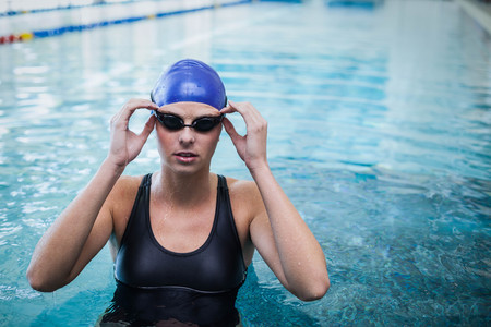 swim cap: Fit woman wearing swim cap and goggles in the water at the pool