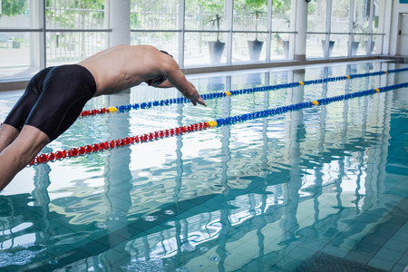 lane marker: Fit man diving in the water at the pool